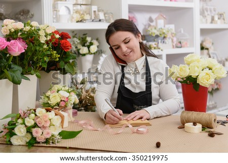 Portrait of smiling florist standing near the table with flowers talking on phone