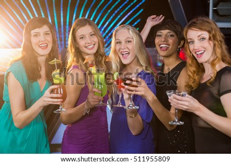 Portrait of smiling friends having glass of cocktail at counter in bar