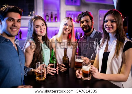 Portrait of smiling friends holding beer bottle and beer glass at bar counter in bar
