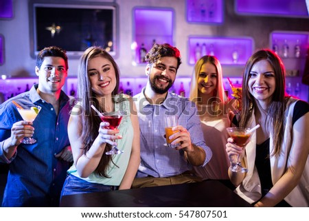 Portrait of smiling friends showing cocktail at bar counter in bar