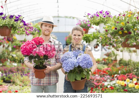 Portrait of smiling gardeners holding flower pots at greenhouse - stock photo