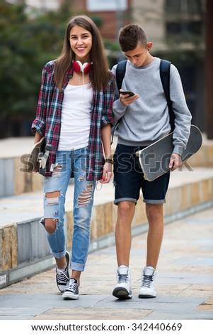 Portrait of smiling girl and boy teenagers walking with skateboards outdoors 