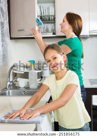 Portrait of smiling girl and european mom tidy kitchen up - stock photo