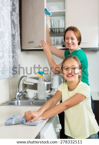 Portrait of smiling girl and mom cleaning kitchen up - stock photo