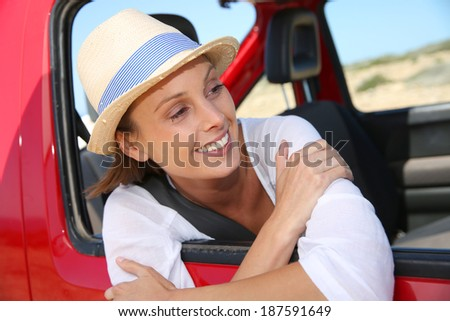 Portrait of smiling girl at red car window
