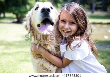 Portrait of smiling girl embracing her dog in the park - stock photo