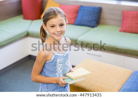 Portrait of smiling girl holding a book in library at school - stock photo