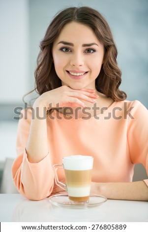 Portrait of smiling girl in peach blouse  sitting at the table with glass of coffee on grey background. - stock photo