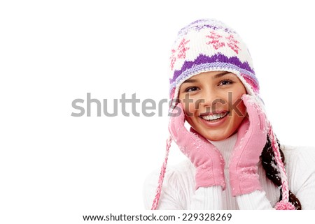 Portrait of smiling girl in pink gloves and knitted winter cap in isolation - stock photo