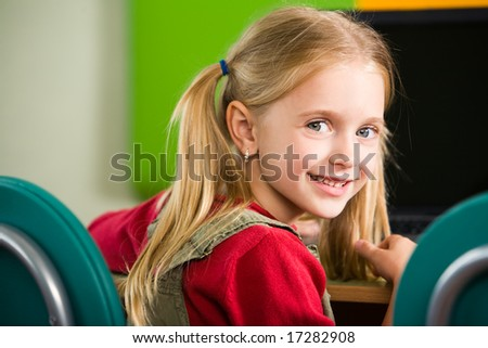 Portrait of smiling girl looking at camera while sitting at her place - stock photo