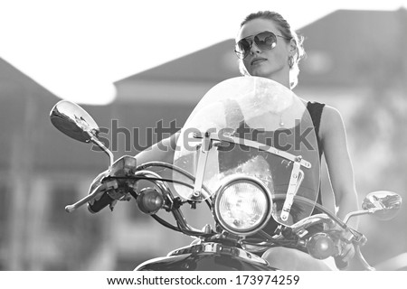 Portrait of smiling girl on scooter holding a helmet - Outdoor on street .Retro shot. Fashion art photo .B&W. - stock photo