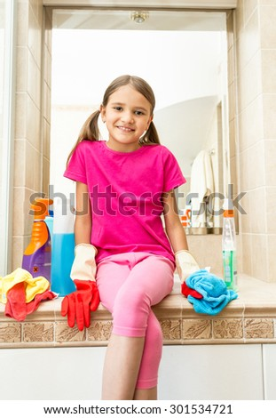 Portrait of smiling girl sitting on sink at bathroom while doing cleaning