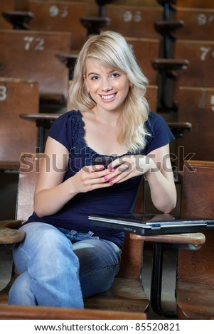 Portrait of smiling girl using cell phone - stock photo
