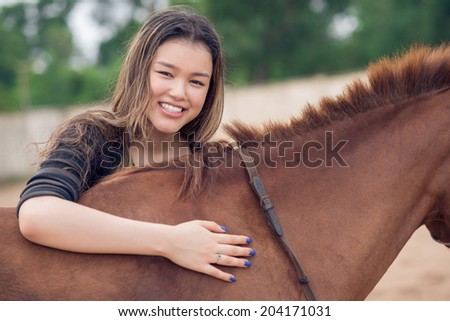 Portrait of smiling girl with a bay horse - stock photo