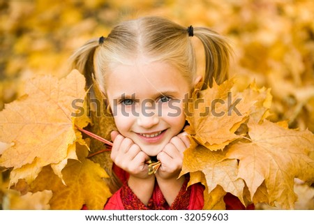 Portrait of smiling girl with dry maple leaves looking at camera - stock photo
