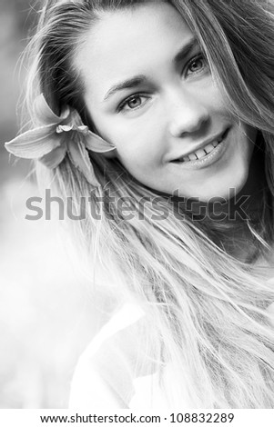 Portrait of smiling girl with lily flower in hair
