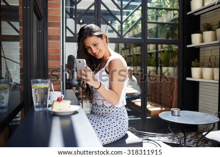 Portrait of smiling gorgeous female taking picture of cappuccino cup and berries cake with her smart phone camera, attractive appearance young woman using her cellphone while photographing breakfast - stock photo