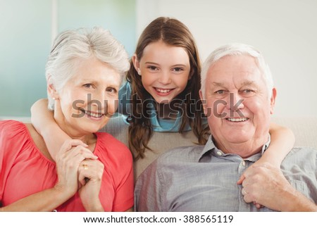 Portrait of smiling granddaughter embracing her grandparents in living room - stock photo