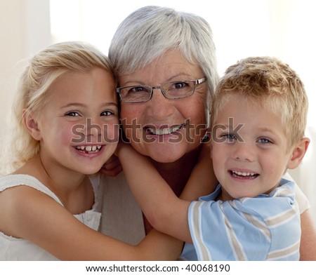 Portrait of smiling grandmother and grandchildren hugging - stock photo