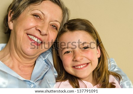 Portrait of smiling grandmother and granddaughter - stock photo