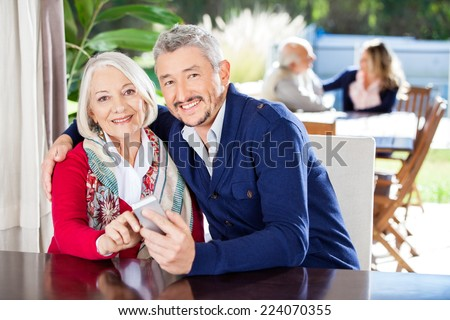 Portrait of smiling grandmother and grandson using smartphone with family in background at nursing home - stock photo