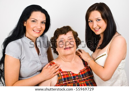 Portrait of smiling grandmother with her two granddaughter  standing together - stock photo