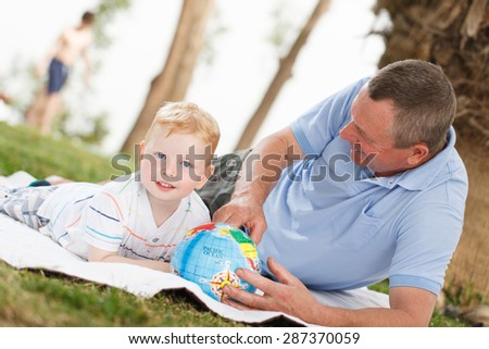 Portrait of smiling grandson and grandfather with globe - stock photo