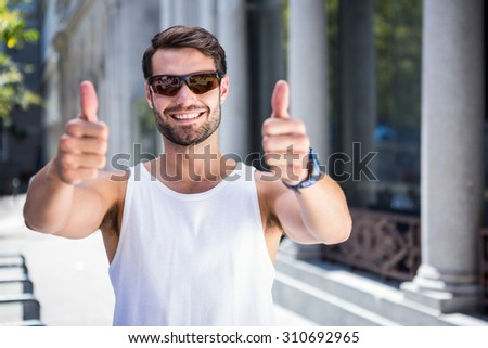 Portrait of smiling handsome athlete doing thumbs up in the city - stock photo