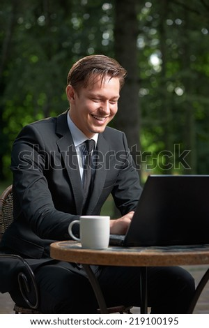 Portrait of smiling handsome businessman sitting at cafe table using his laptop. - stock photo