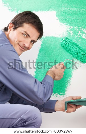 Portrait of smiling handsome man painting his house with roller