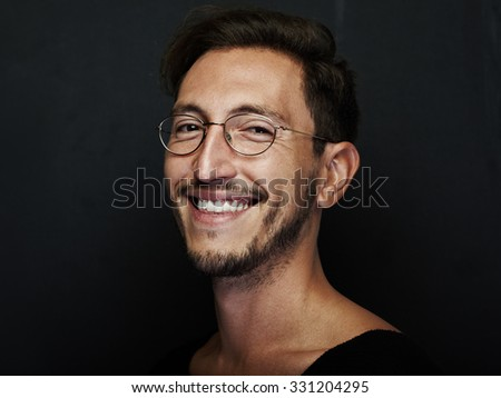 Portrait of smiling handsome man wearing glasses and looking at the camera. Horizontal