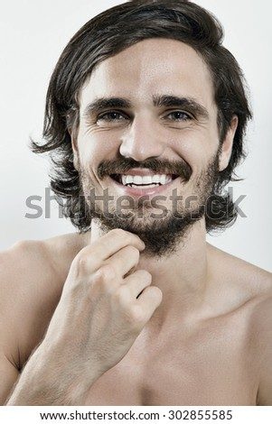 Portrait of smiling handsome young man against white background - stock photo
