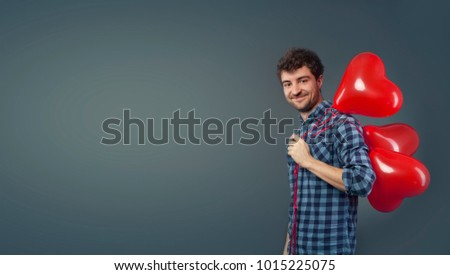 Portrait of Smiling Handsome young man holding bunch of heart shaped air balloons and laughing. Happy Joyful Family. Love. Happy Valentine's Day