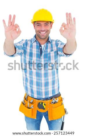 Portrait of smiling handyman gesturing okay on white background - stock photo