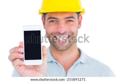 Portrait of smiling handyman showing smart phone on white background - stock photo
