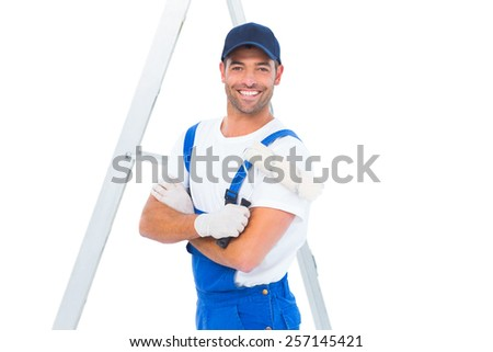 Portrait of smiling handyman with paint roller standing by ladder on white background