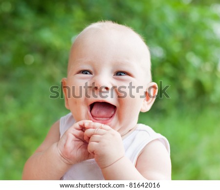 Portrait of smiling happy baby boy on natural background in summer