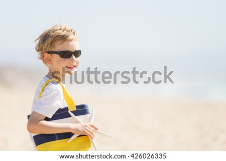 portrait of smiling happy boy in sunglasses holding beach bag and starfish enjoying summer vacation, copyspace on the side - stock photo