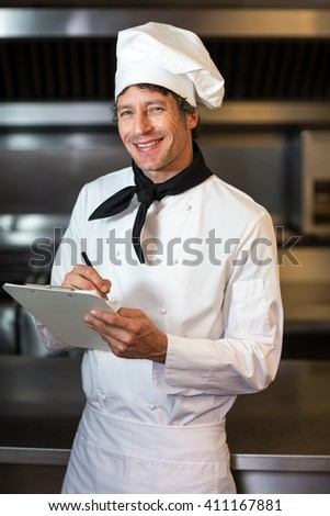 Portrait of smiling happy chef writing on clipboard in commercial kitchen