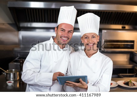 Portrait of smiling happy chefs holding clipboard in commercial kitchen - stock photo