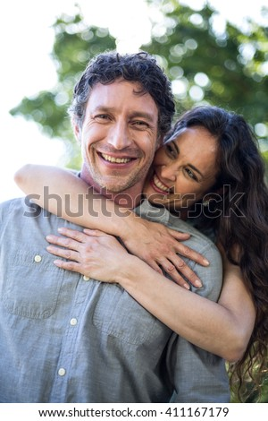 Portrait of smiling happy husband being hugged by wife at park - stock photo
