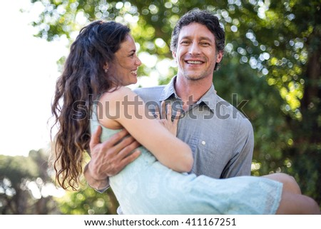 Portrait of smiling happy husband carrying wife at park - stock photo