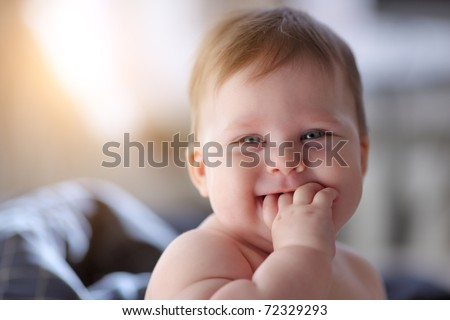Portrait of smiling happy 7 month old baby girl indoors. Closeup, shallow DOF. - stock photo