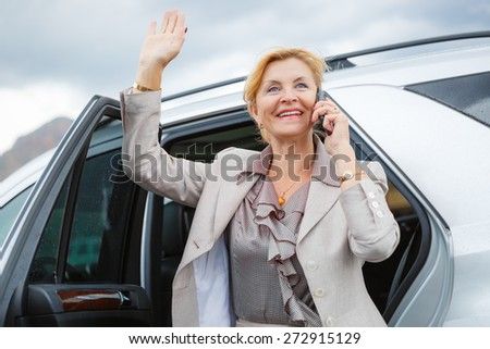 Portrait of smiling happy old senior business woman 60-65 years, waving his hand and talking on the mobile phone - stock photo
