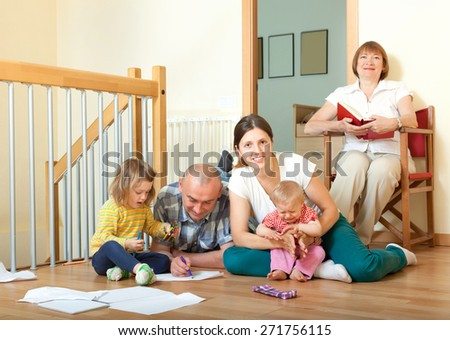 Portrait of  smiling happy three generations family sits on parquet floor in livingroom at home - stock photo