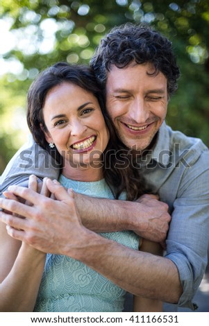 Portrait of smiling happy wife being hugged by husband at park - stock photo