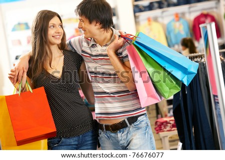 Portrait of smiling husband and wife looking at each other in the mall - stock photo