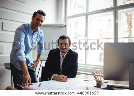 Portrait of smiling interior designer with coworker working on blueprint in office - stock photo