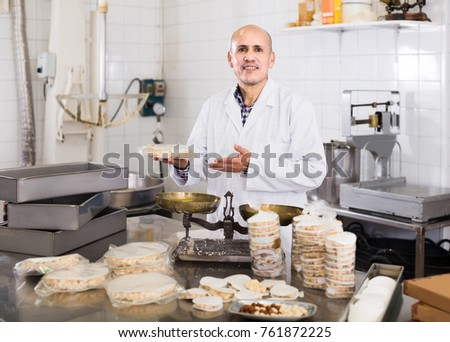 Portrait of smiling italian mature male with packing of turron in food factory