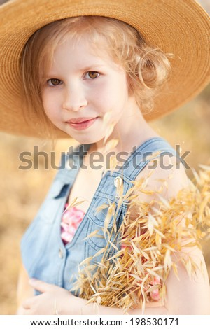Portrait of smiling kid girl wearing hat outdoors - stock photo
